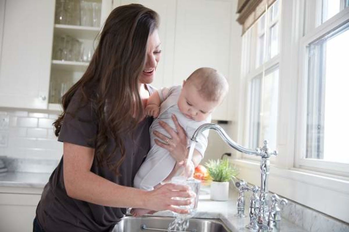 Woman holding baby at the kitchen sink while filling up a cup with water