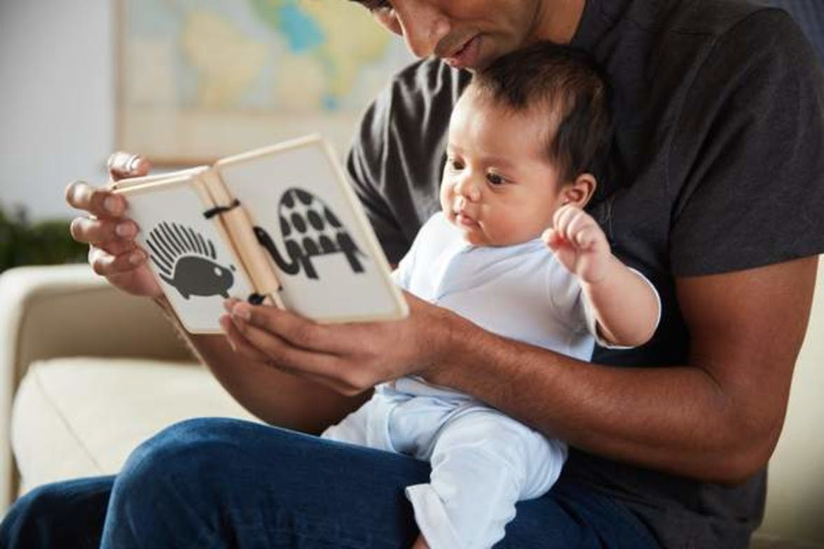 Man sitting with a baby on his lap looking at the Black and White Contrast Cards by Lovevery