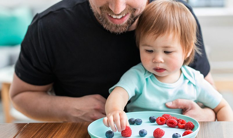 Father and daughter sort berries on a plate.