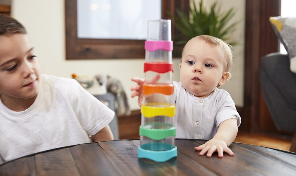 Baby plays with stacking tower, while older child looks on.