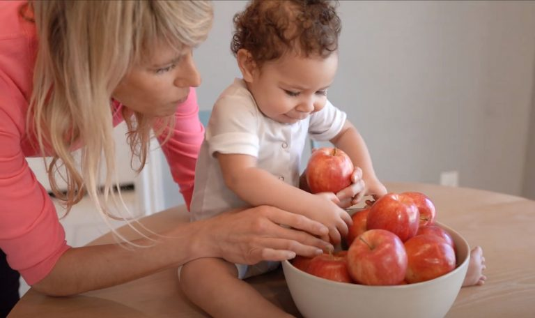 Baby looking at a bowl of apples and picking one up