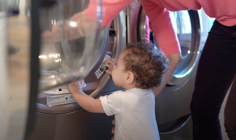 Baby looking into a washing machine