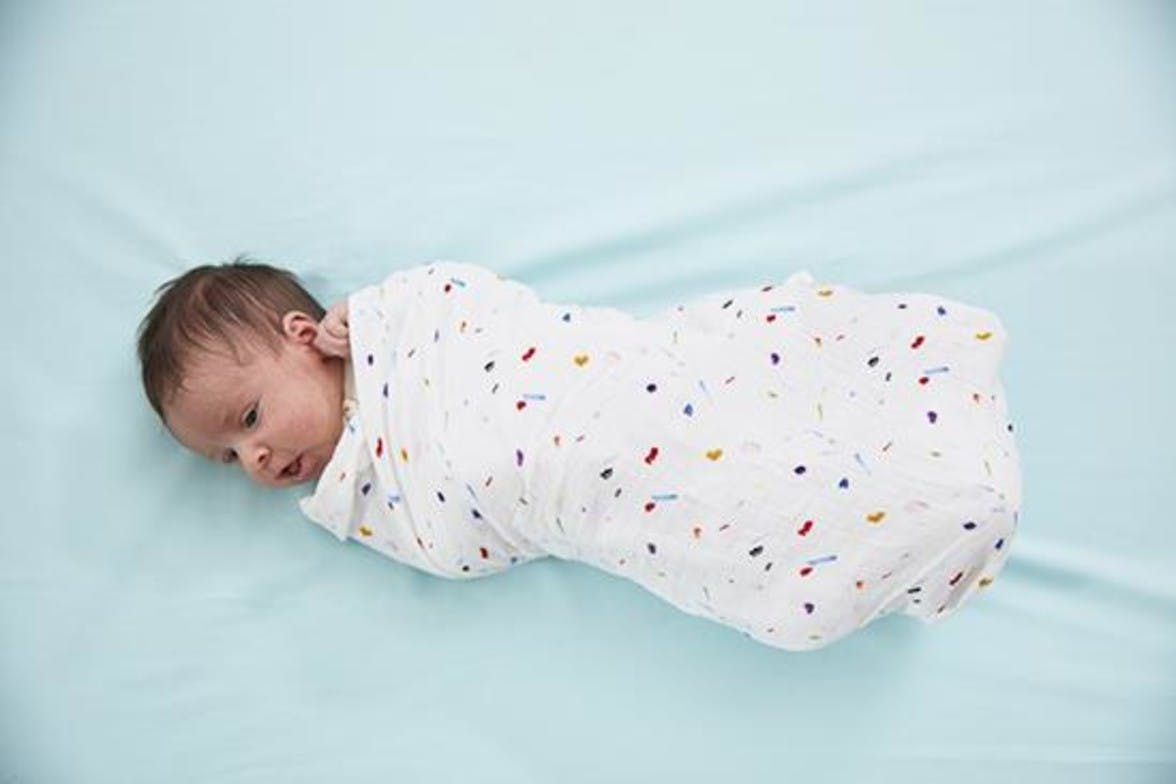 Baby laying down wrapped in an organic cotton swaddle by Lovevery