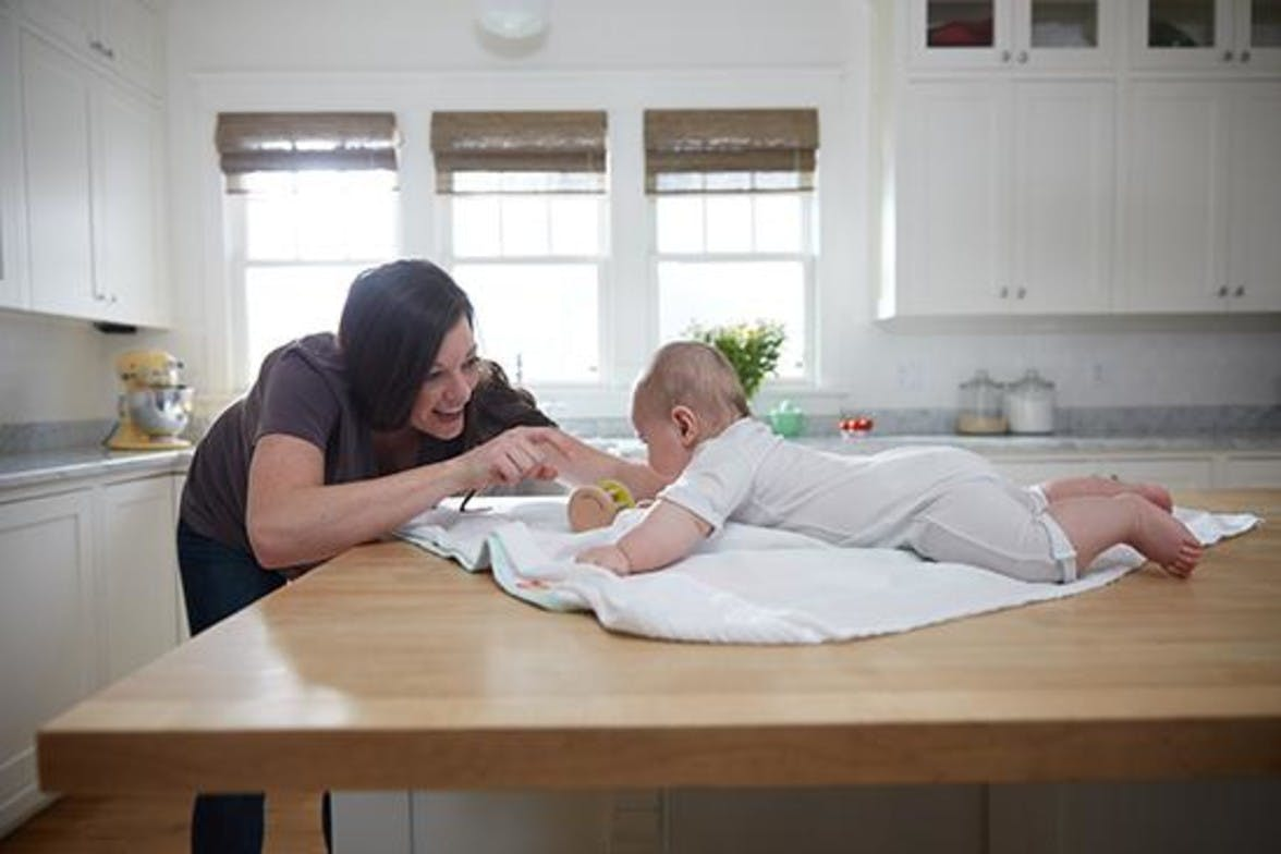 Woman getting a babies attention while doing tummy time on the kitchen table
