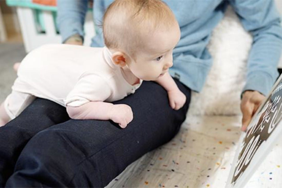 Baby doing tummy time on a woman's lap looking at Black and White cards by Lovevery