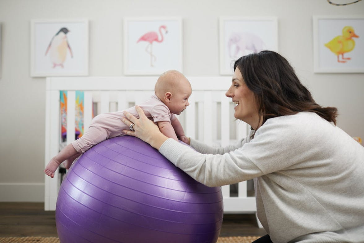 Baby doing tummy time on an exercise ball being supported by a woman