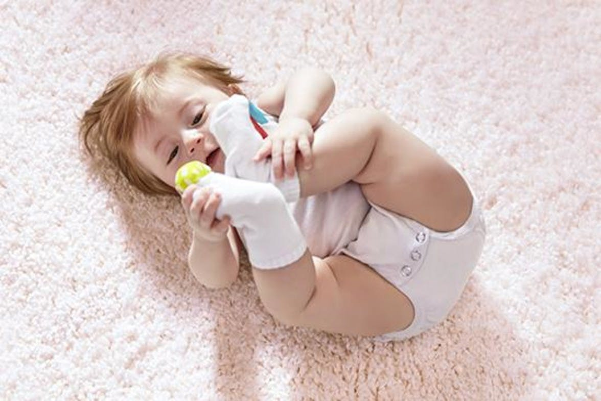 Baby laying on the carpet looking up at their feet that have rattle socks on