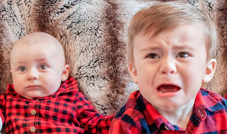 A baby and an upset young child wearing matching red shirts