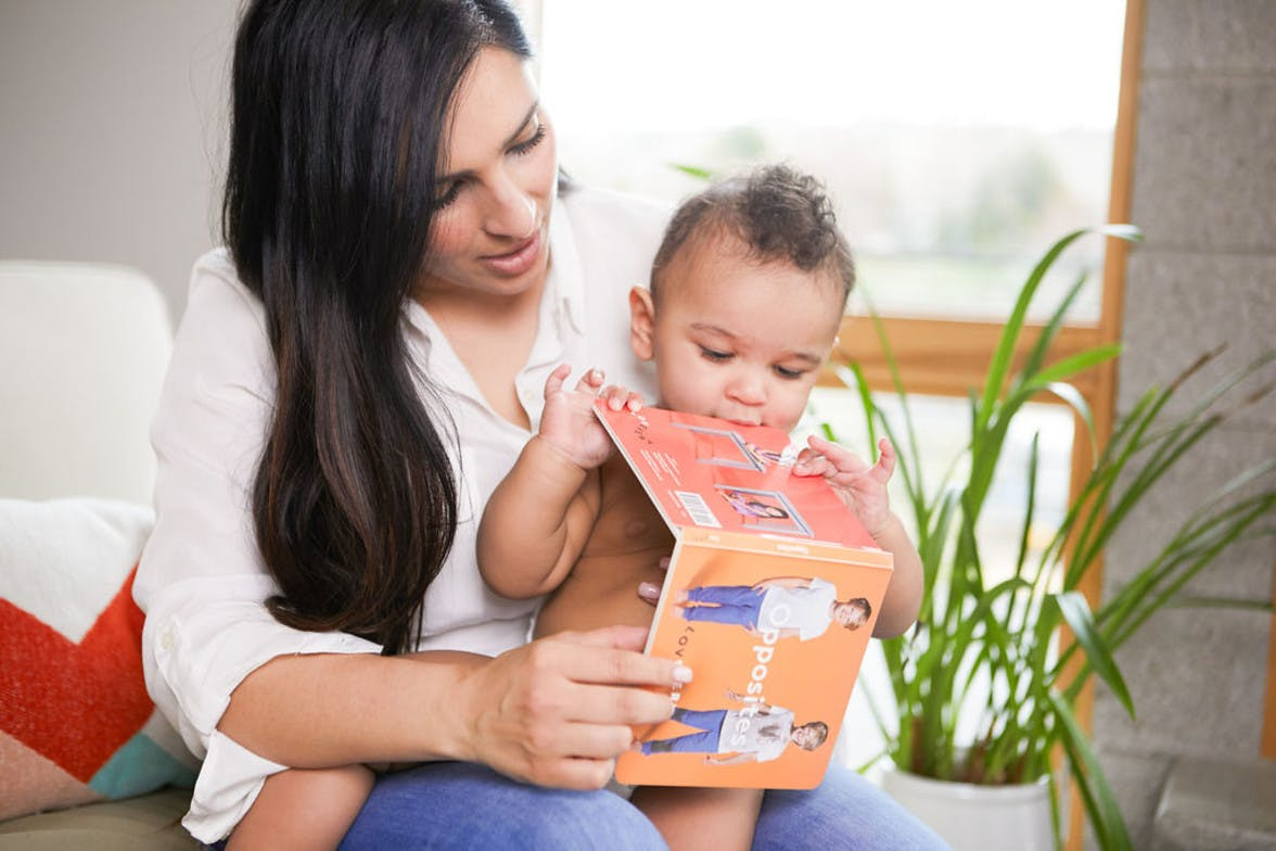 Woman holding a baby in their lap while looking at a book about opposites by Lovevery.