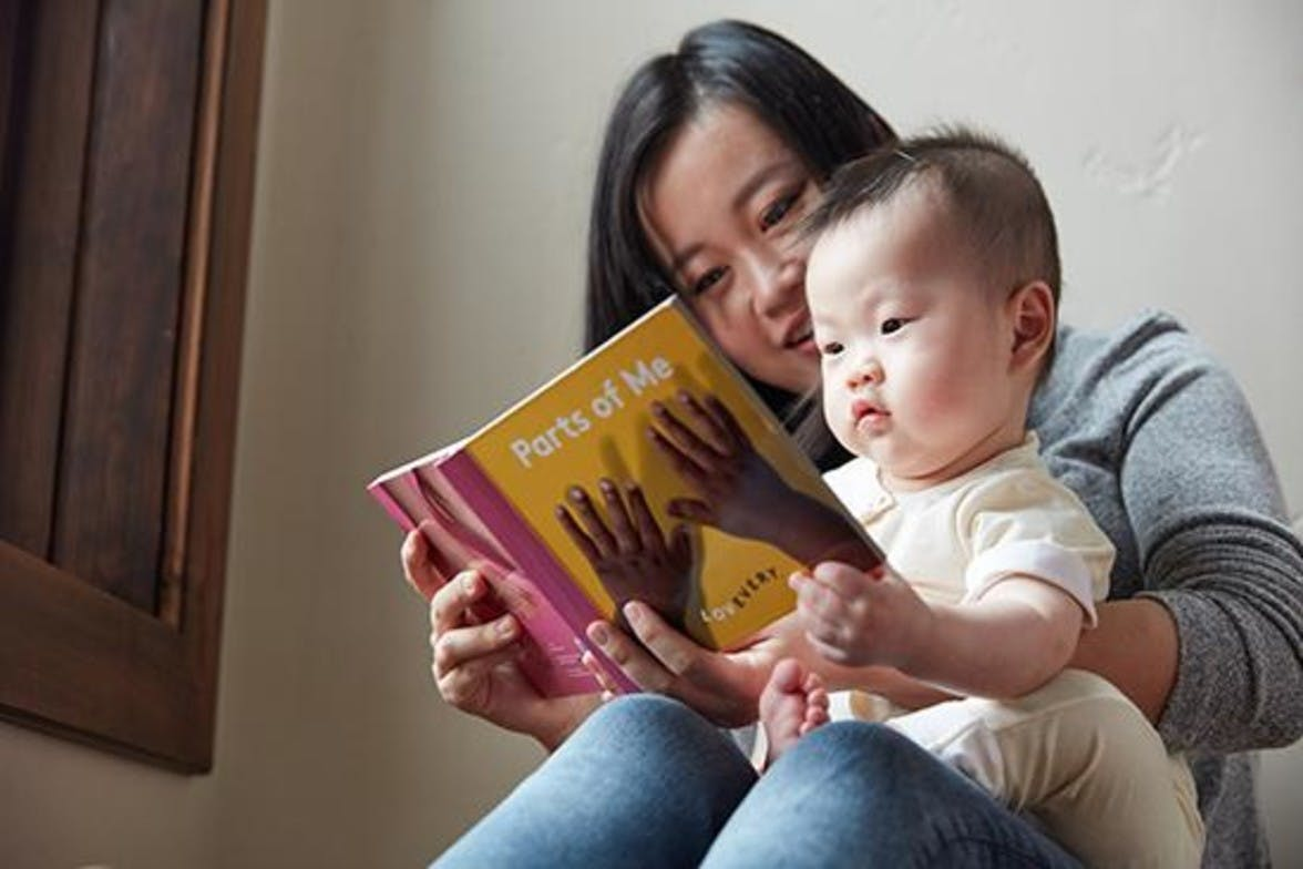 Woman holding a baby in their lap while looking at a book about body parts by Lovevery.