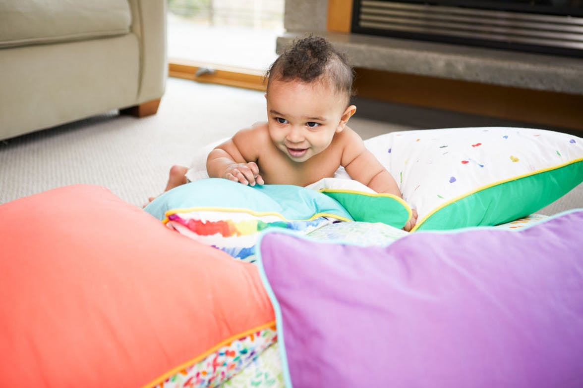 A baby crawling on several pillows on the floor