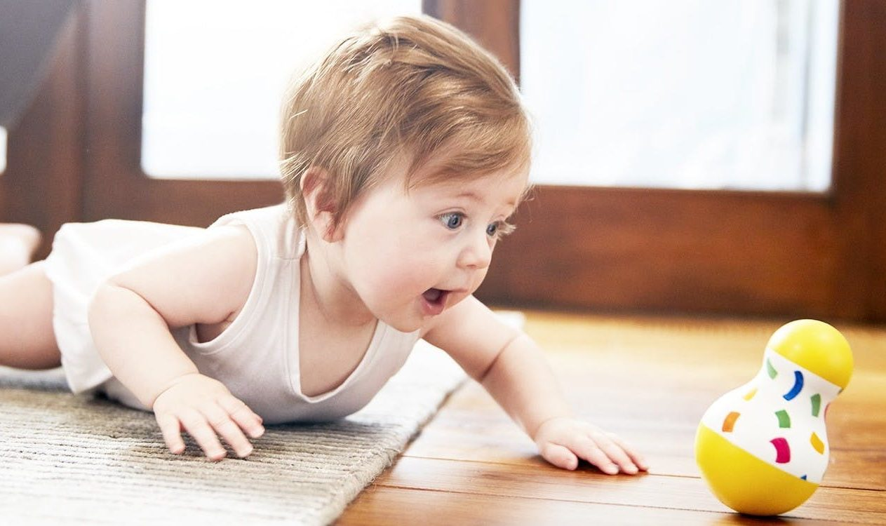 Baby doing tummy time and looking at a wobble toy from Lovevery