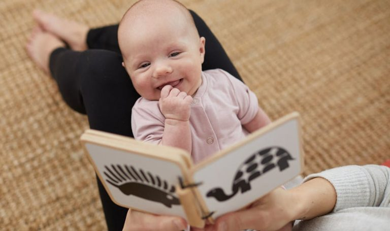 Baby laying on woman's knees looking at the Wooden Book by Lovevery