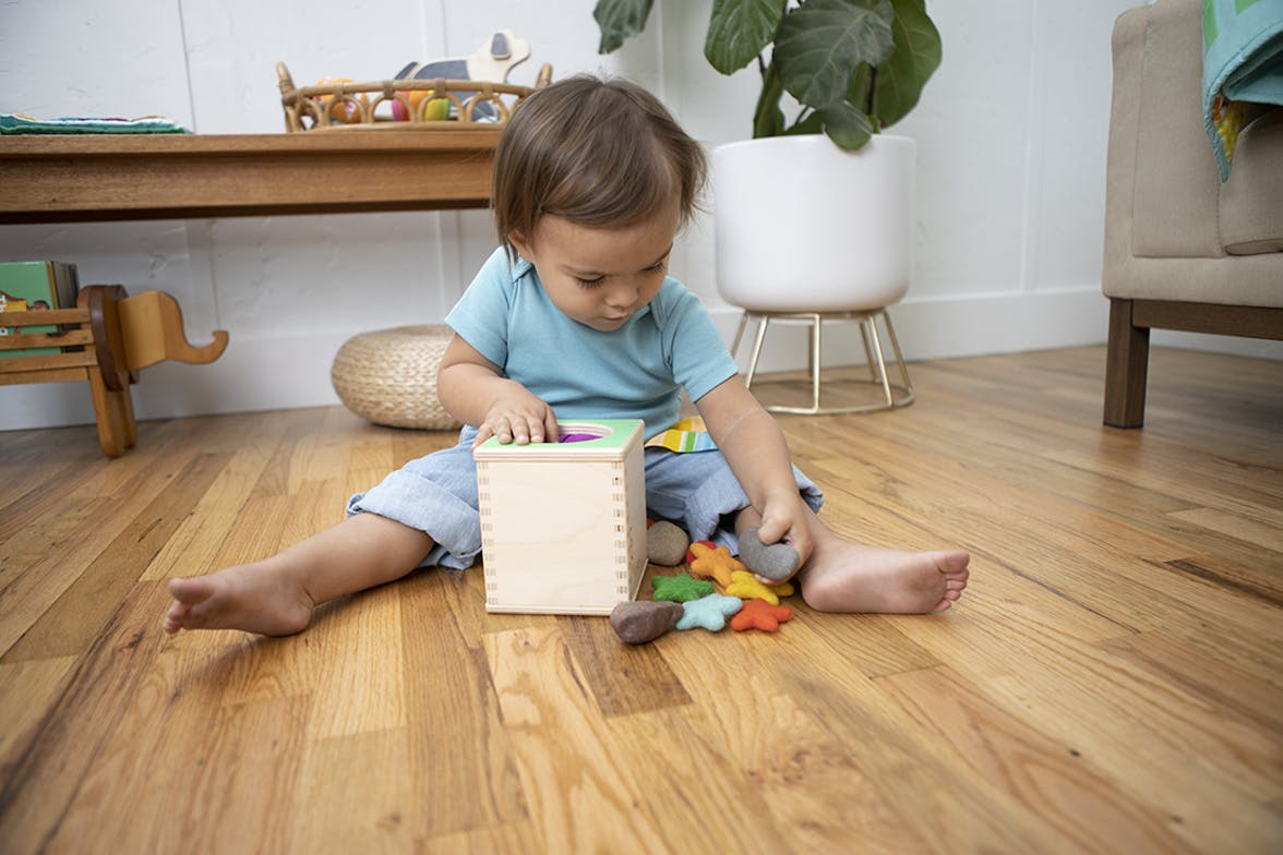 Toddler using the Magic Tissue Box by Lovevery with rocks