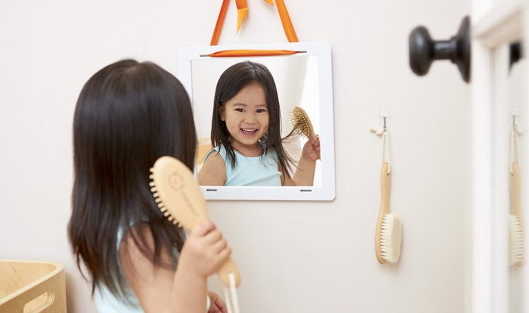 Young child looking at themselves in a mirror while brushing their hair
