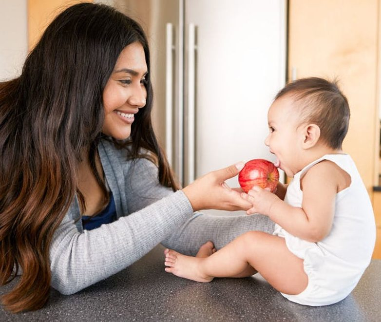 Woman helping a baby put an apple up to their mouth