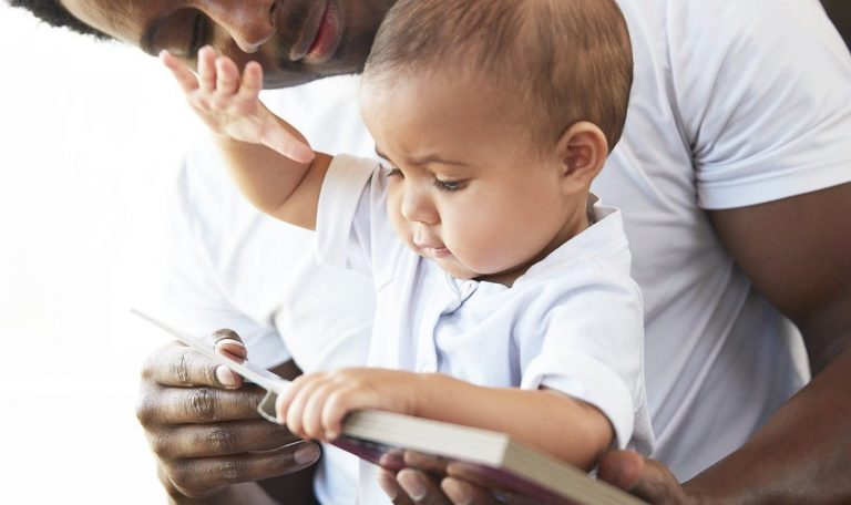 Baby and man looking at a book together