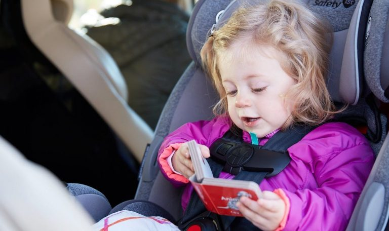 Toddler sitting in a car seat in their car looking at a book by Lovevery