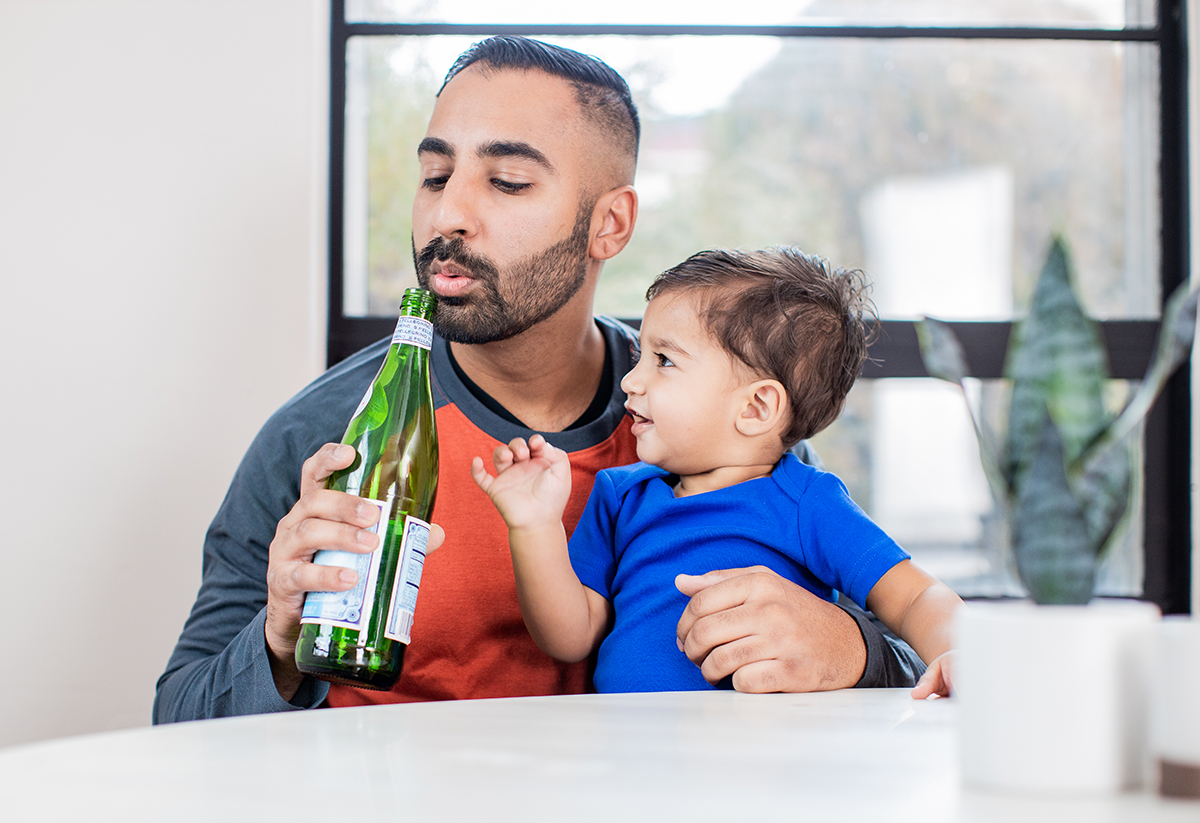 Man holding a toddler and blowing into a glass bottle to make a noise
