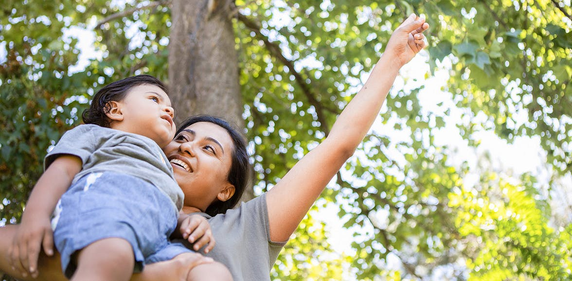 Woman holding a toddler outside pointing at the sky