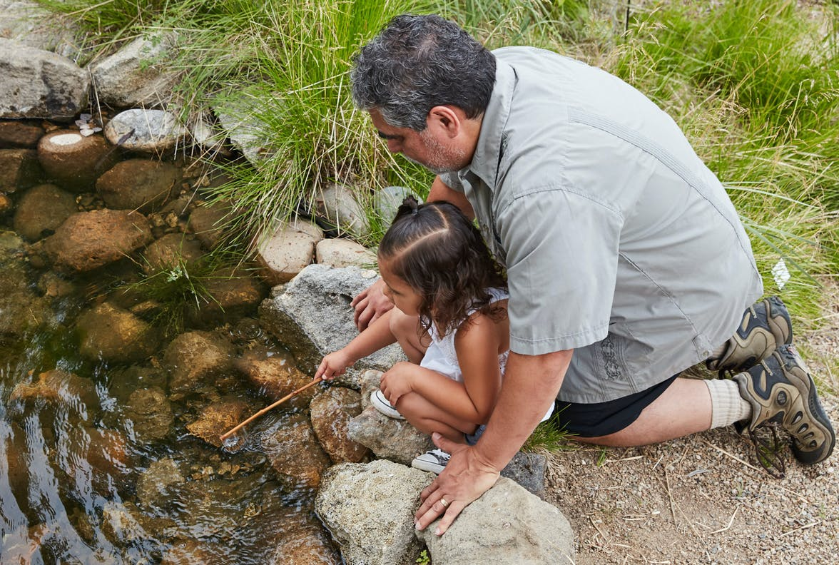 Man sitting outside with a young child putting a stick in a pond