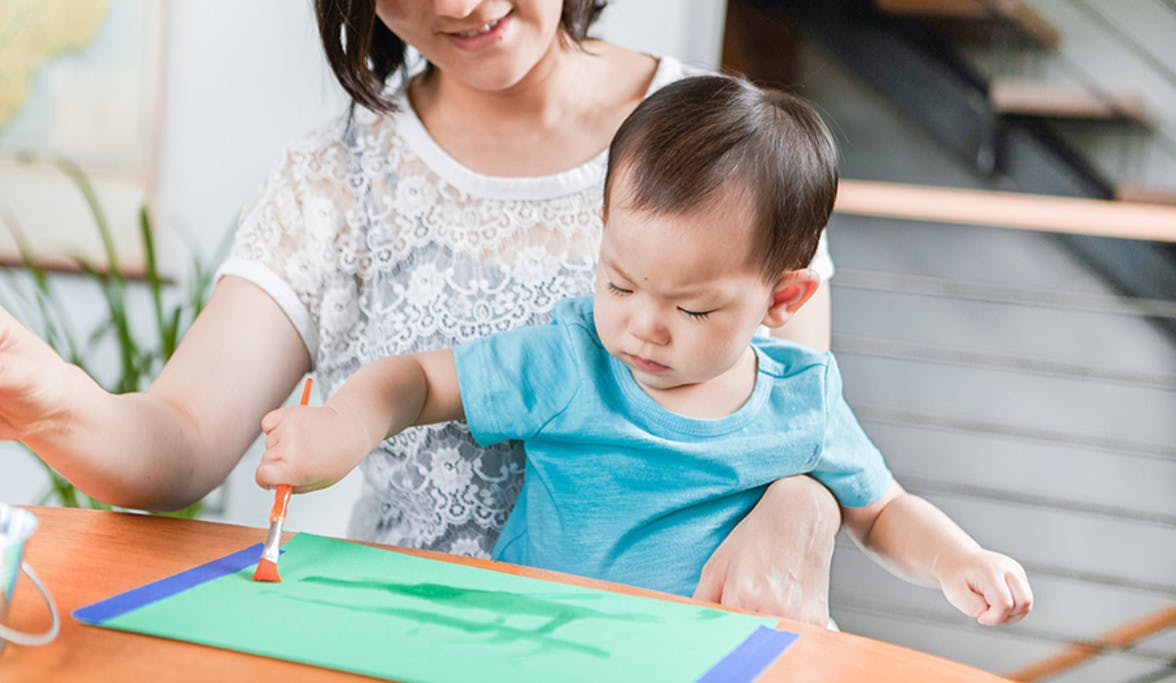 Woman sitting with a toddler on her lap while they are painting with water