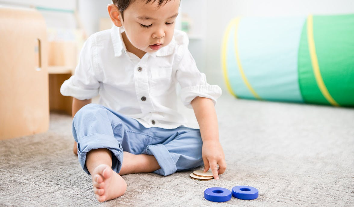 Toddler sitting up looking at wooden coins and blocks by Lovevery