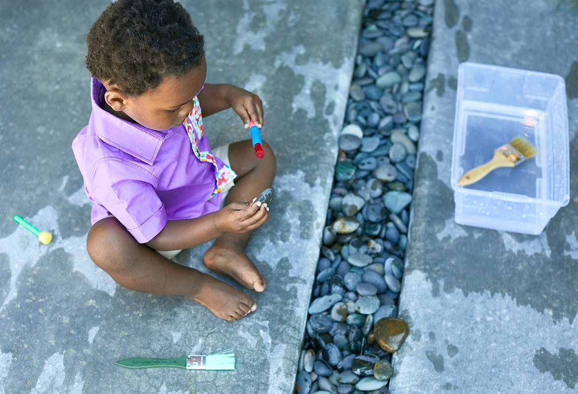 Toddler sitting outside playing with water and rocks