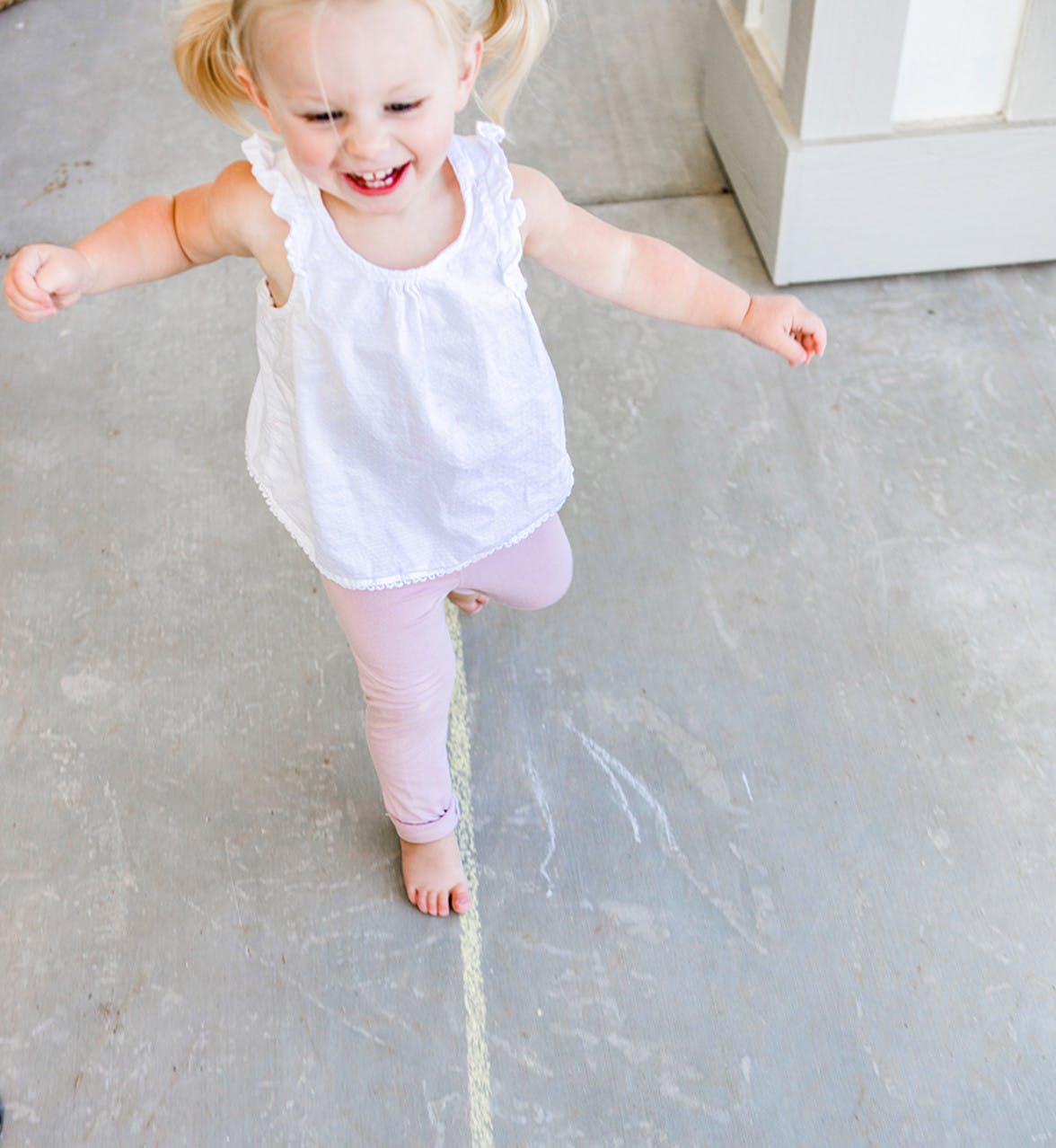 Young child walking on a line of chalk outside