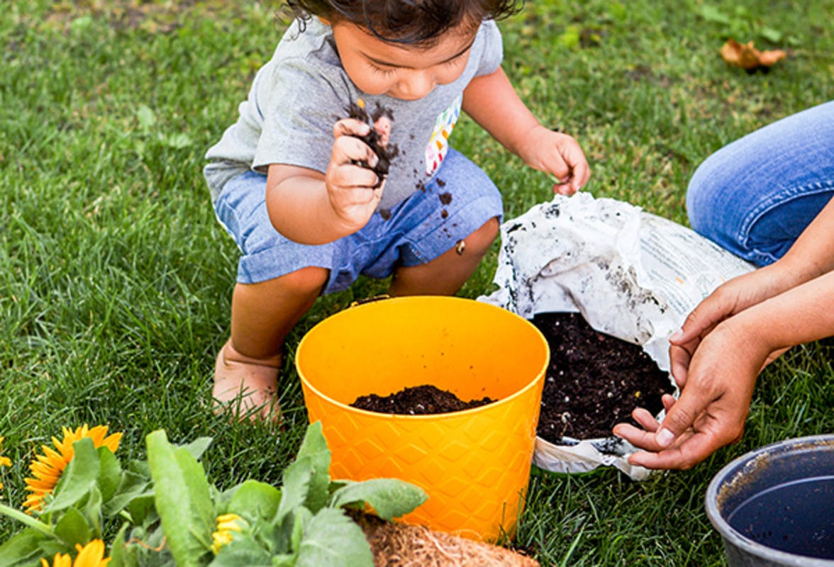 Young child outside putting dirt into an orange pot