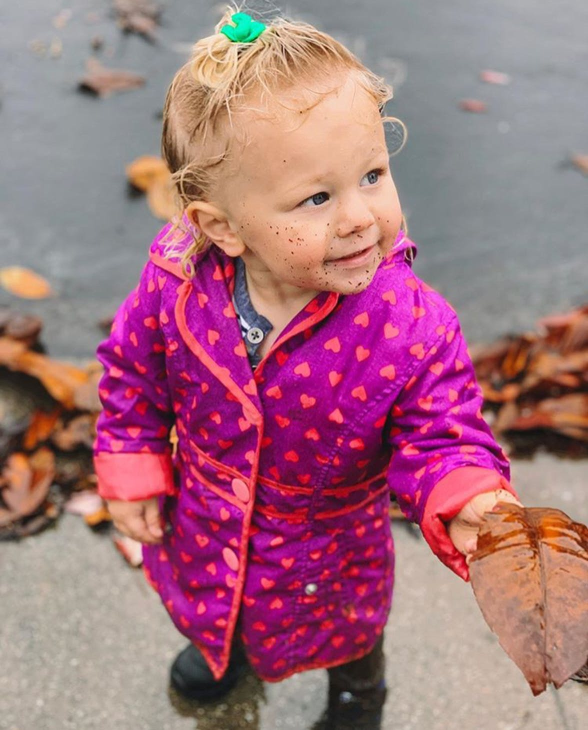 Toddler standing outside with dirt on their face while holding a leaf