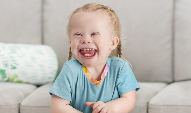 Toddler in a blue shirt smiling and laughing