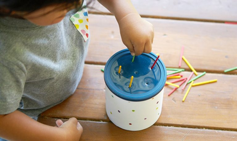 Toddler placing colorful wooden sticks into a container