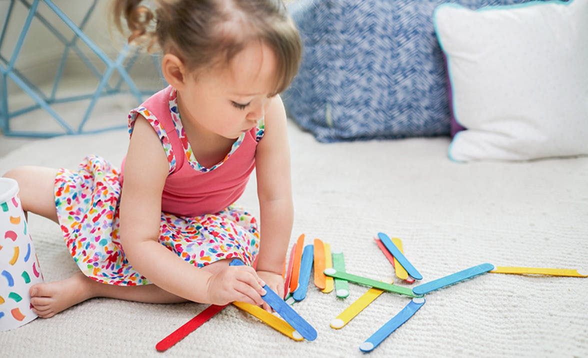 Toddler playing with colored popsicle sticks that have Velcro on the ends