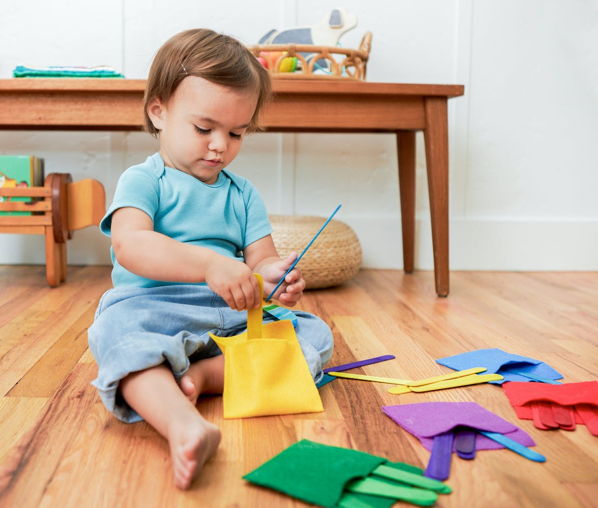 Toddler putting colored popsicle sticks into colored felt pockets