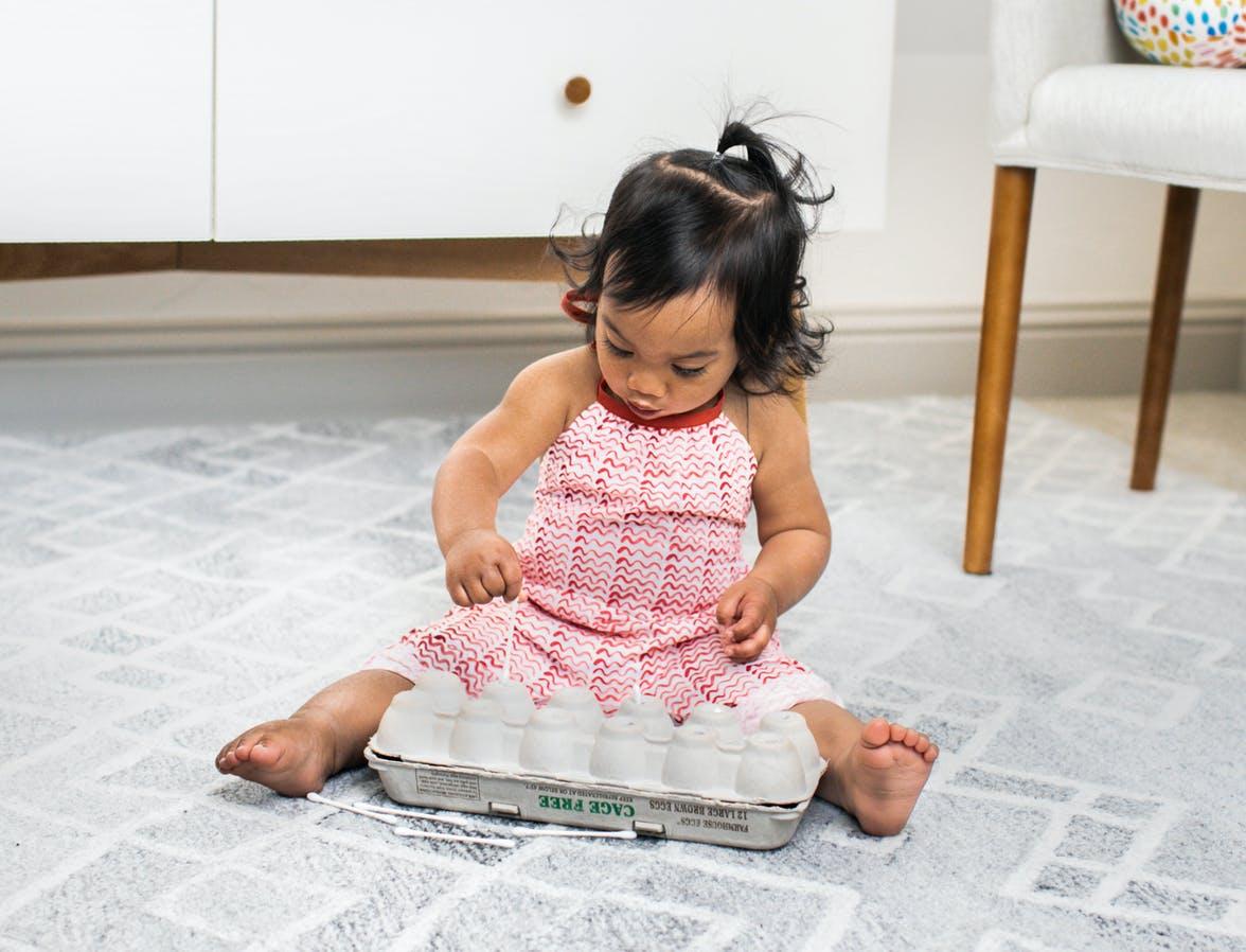 Toddler putting q-tips into an egg carton