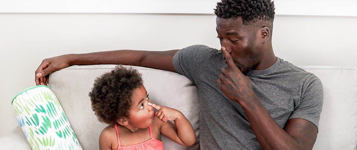Toddler and Man sitting on the couch both touching their noses