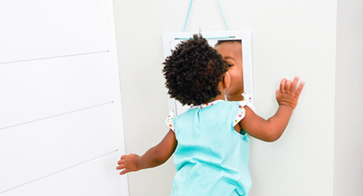 Toddler looking into a mirror at themselves