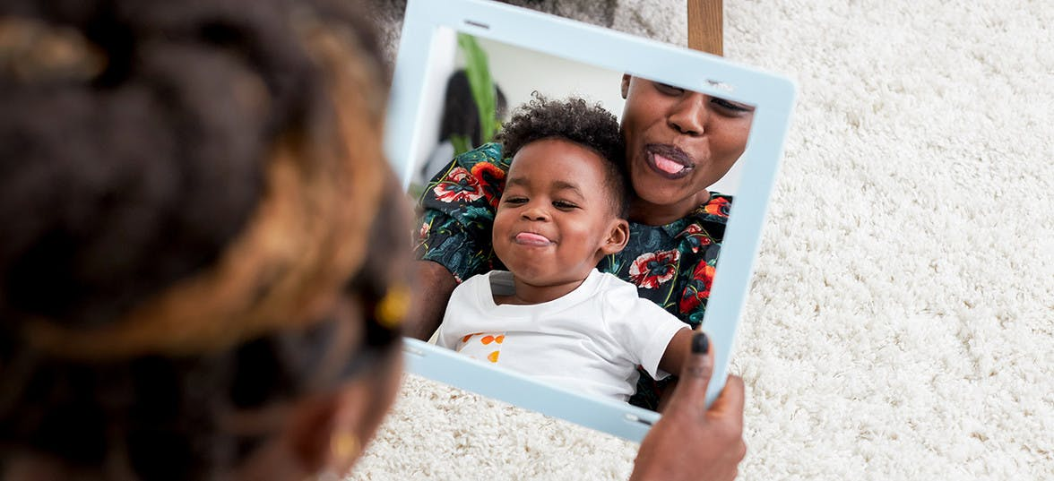 Woman with a toddler in her lap looking into a mirror sticking out their tongues