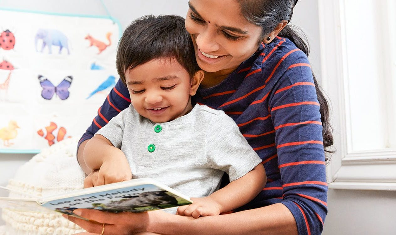 Toddler sitting in a woman's lap looking at a book by Lovevery