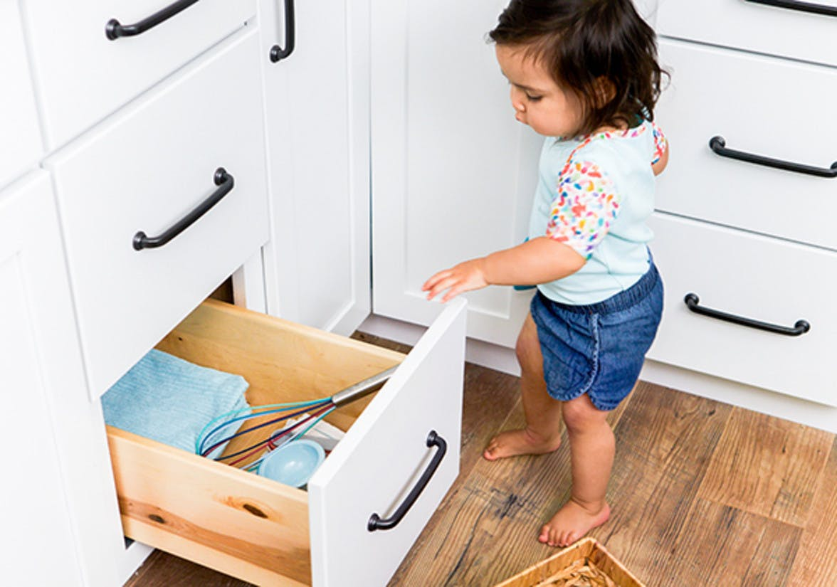 Toddler opening a kitchen cabinet that holds towels and a whisk