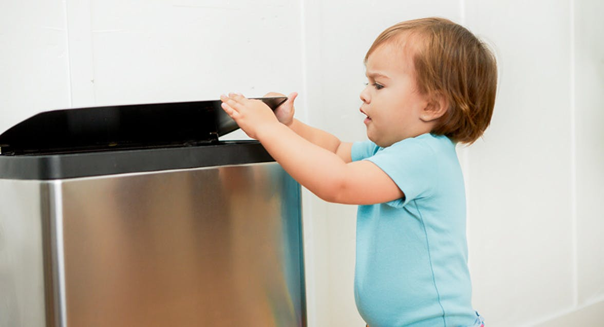 Young child closing the kitchen trashcan.