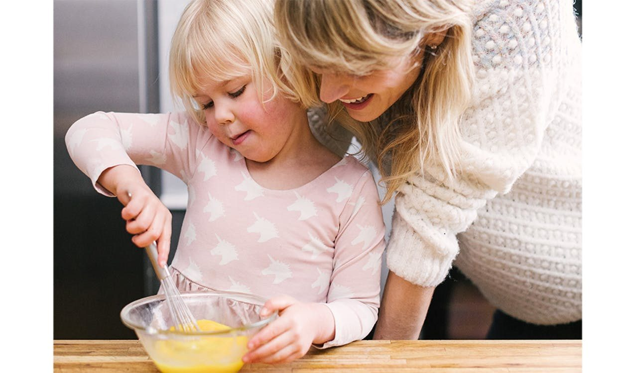 Jessica Rolph, Co-founder and CEO of Lovevery, in the kitchen with her daughter stirring liquid in a bowl