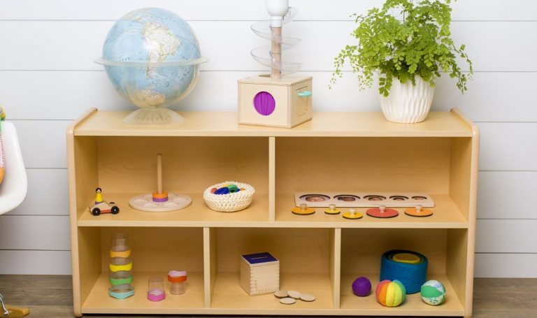 Lovevery items on a wooden shelf