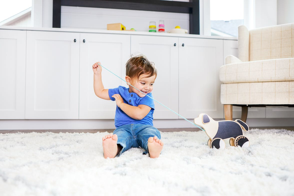 Toddler sitting on a rug pulling the Pull Pup by Lovevery