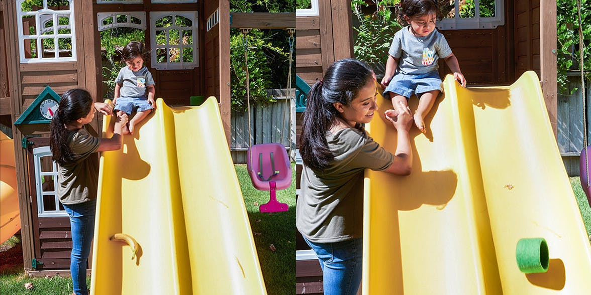 Woman helping a toddler down a yellow slide