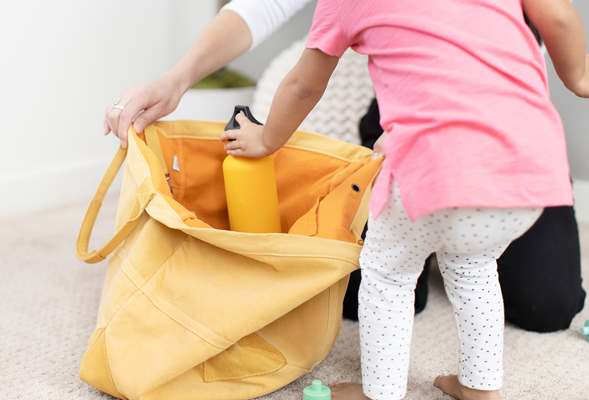 Young child putting a water bottle into a yellow bag