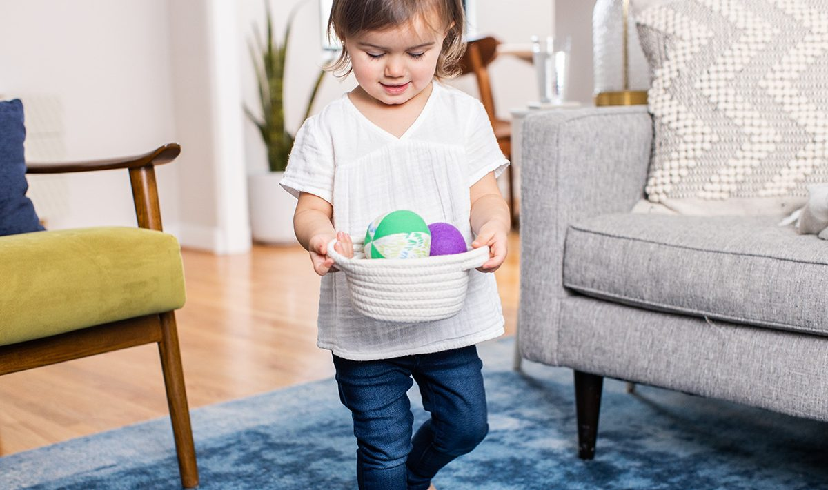 Young child carrying a basket filled with colorful balls