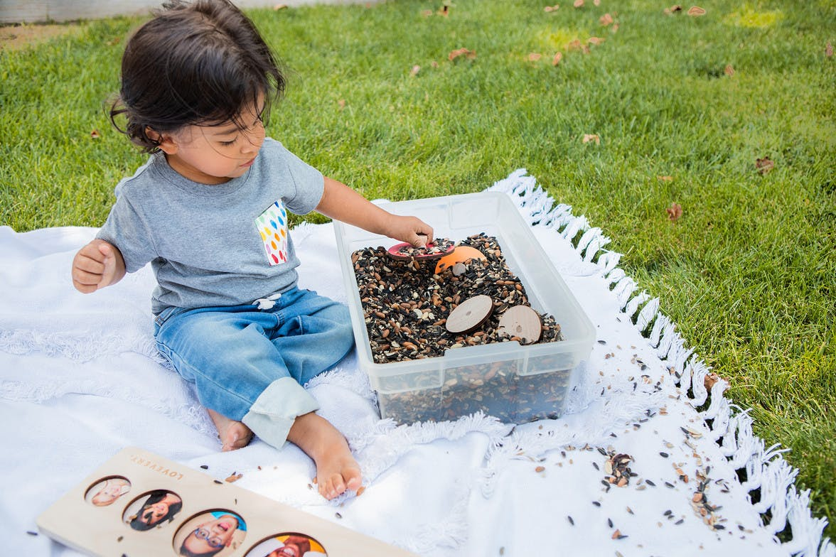 Toddler sitting outside with a container of seeds with puzzle pieces hidden in them