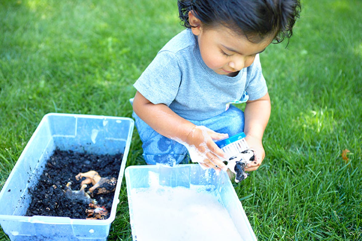 Toddler playing outside with a container of dirt with animal figurines and they're cleaning them off